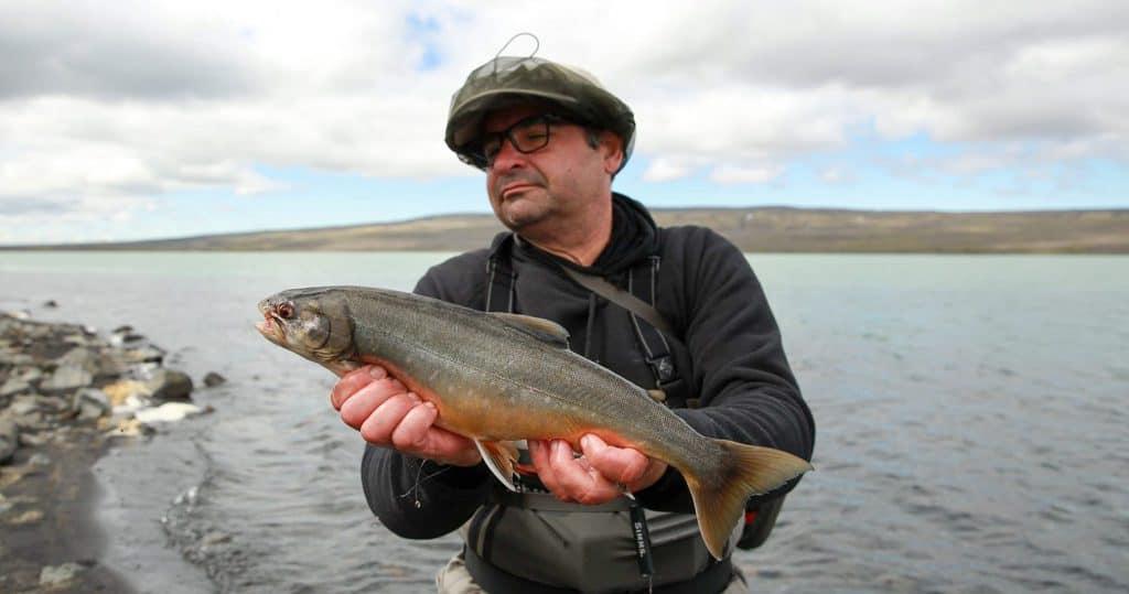 a man holding an arctic char from the spörðuöldulón highland reservoir